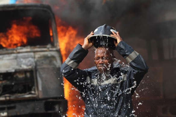 Image- Fireman, fire truck shows a fireman dowsing himself with water in this documentary photography by Akintunde Akinleye