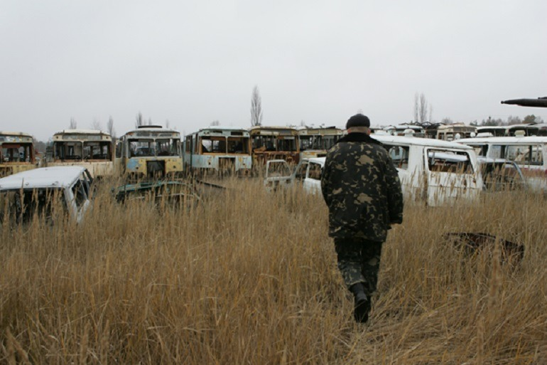 Image- Junk yard- Victor Marushchenko, Chernobyl Zone – Machines Cemetery 2006, shows photos of a junk yard filled with broken buses, cars and trucks