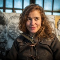 Image- Artist-portrait- Swoon in her studio, Red Hook, Brooklyn, 2013. She stands in front of her very famouse figurative prints