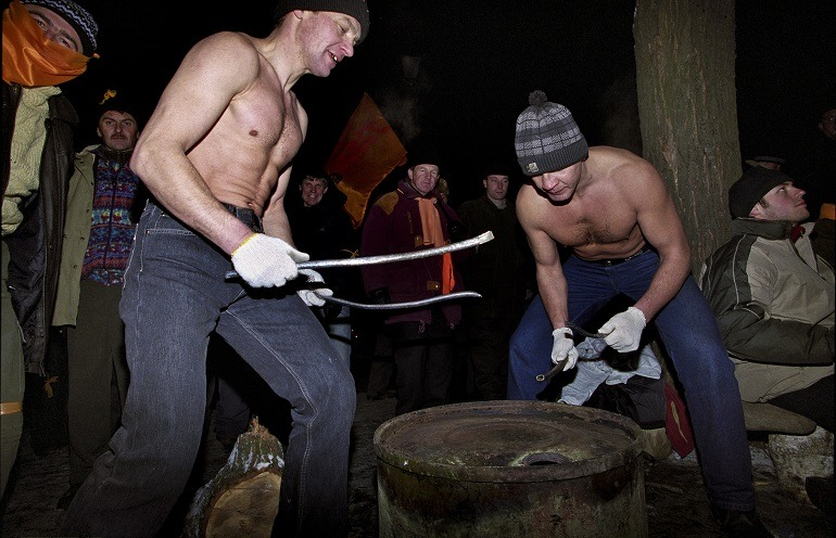 Image-Ukrainian men dancing- Anna Voitenko, Grushevskoho (series) 2004. Entertainment of the audience by two men drumming on a  petroleum drum