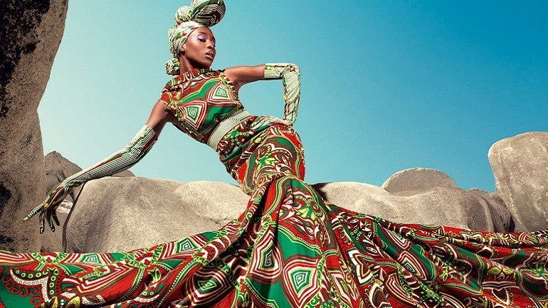 Image: A beautiful women showing off her dress made from wax printed fabrics with bold patterns that has been described as authentic Africa