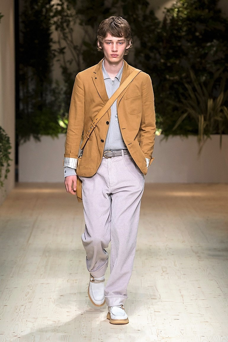 Image: A male model in brown jacket and a gray pant on the runway during the launch of Salvatore Ferragamo Men's Spring Summer 2018 collection -03