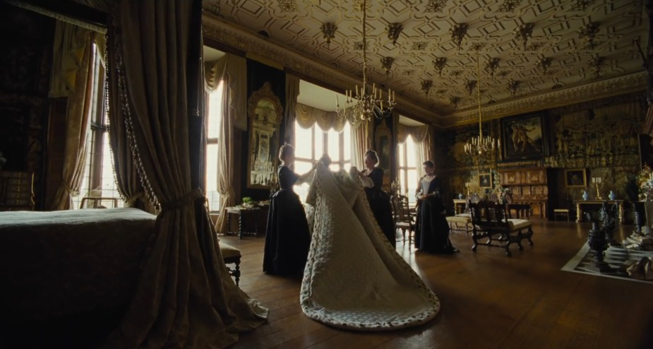 The Favourite- 2018 Film- Queen Anne puts on her cape in a wide shot of her Jacobean bedroom- Best Production Design of 2018