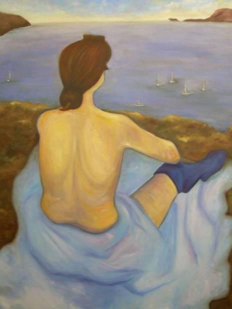 Mujer sentada frente al mar.