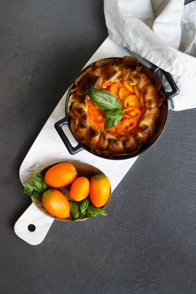 Photograph of seasonal tomato tart in baking pan