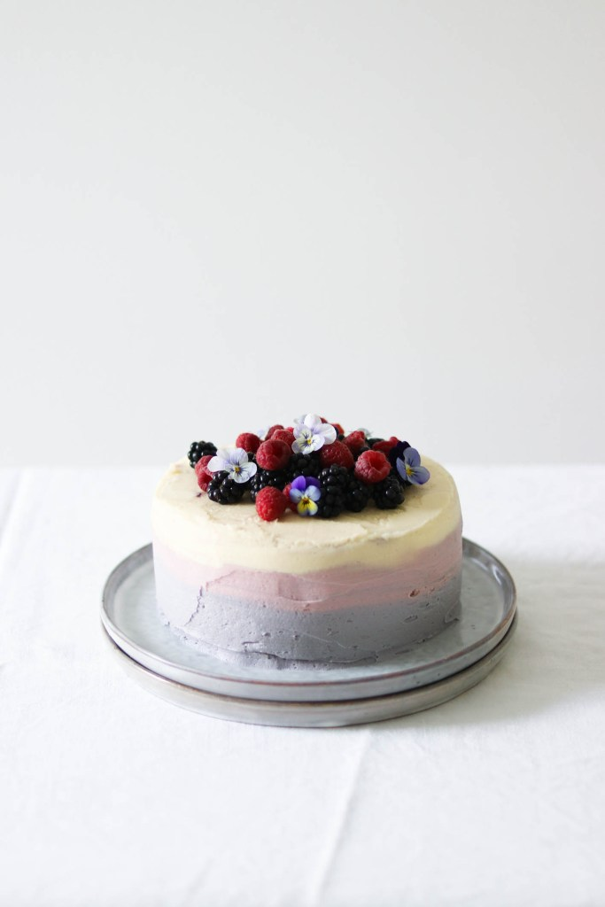 Photograph of blackberry and lemon cake topped with berries and flowers