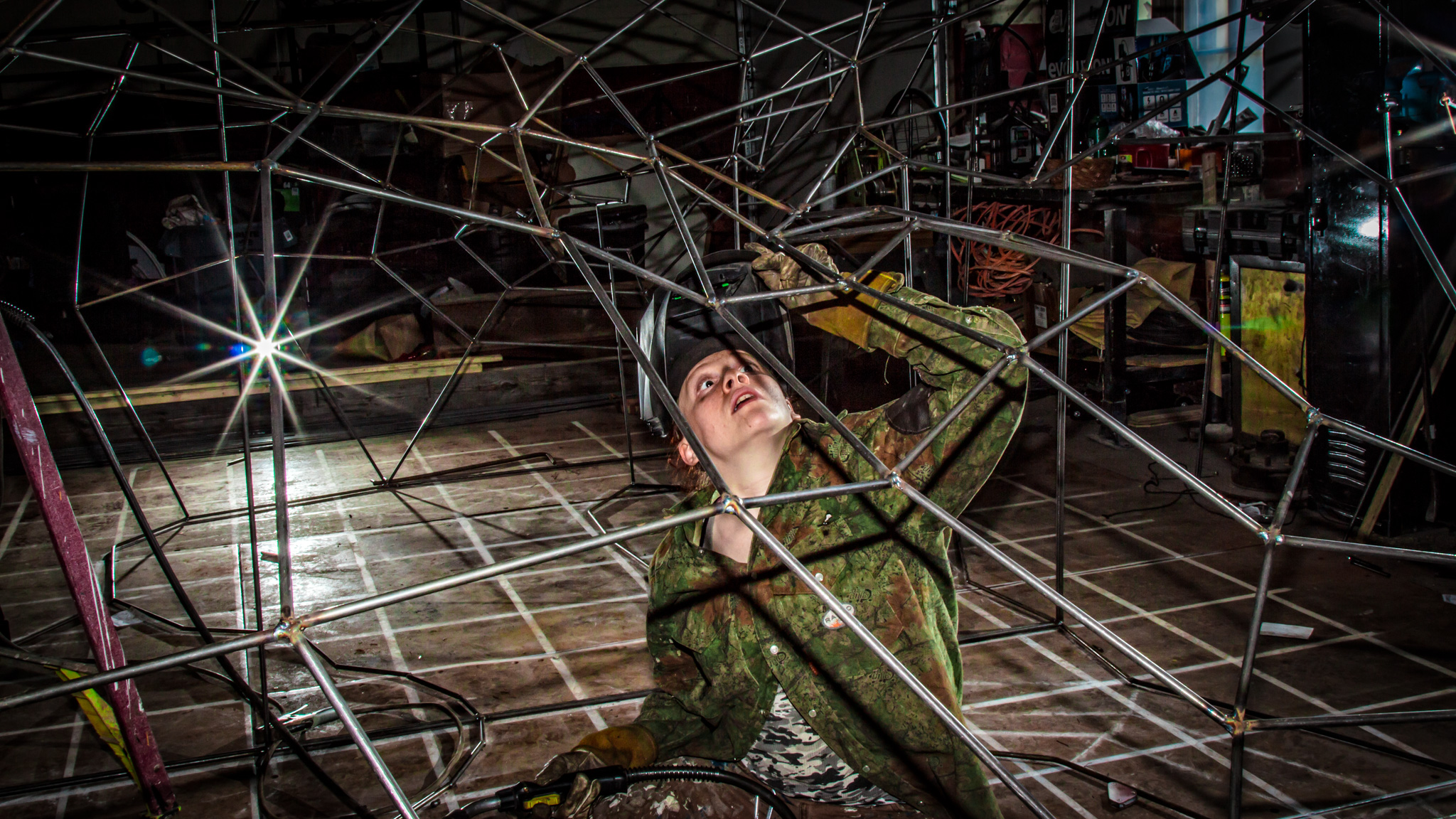 woman inspecting weld wire frame structure artemis boston