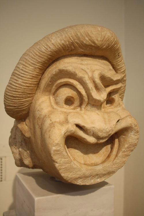 teatro grego; Versão em mármore de uma máscara usada no teatro cômico grego. Essa representava um escravo (século II a.C.) | Encontrado em Atenas, perto do Portão Dipylon (Museu Arqueológico Nacional, Atenas).