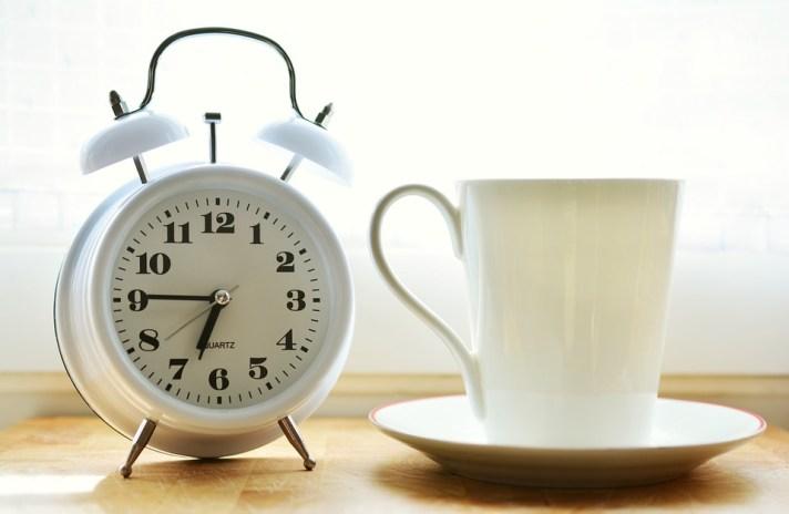 Despertador marcando o horário 6:45 e uma caneca de café.