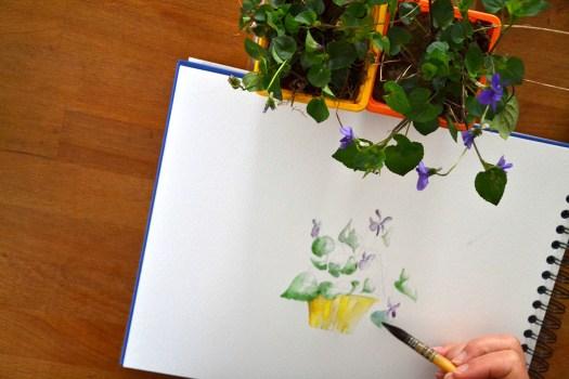 Vue sur un bloc de papier d'aquarelle, sur lequel un pot  de violettes est entrain d'être peint. En bas, à droite, la pointe du pinceau qui se dirige vers le dessin du pot jaune. Les violettes qui servent du modèle sont au dessus du bloc de papier