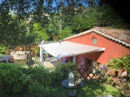 petite maison rouge avec forêt, store sur terrasse vue de coté