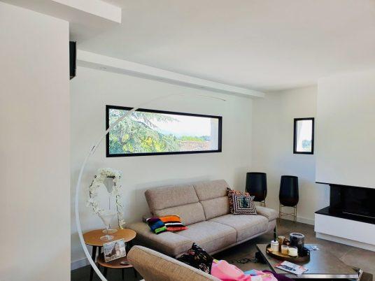 salon moderne avec fenêtre large en aluminium noir