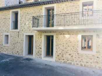 maison en pierre moderne avec fenêtres rectangulaires en PVC