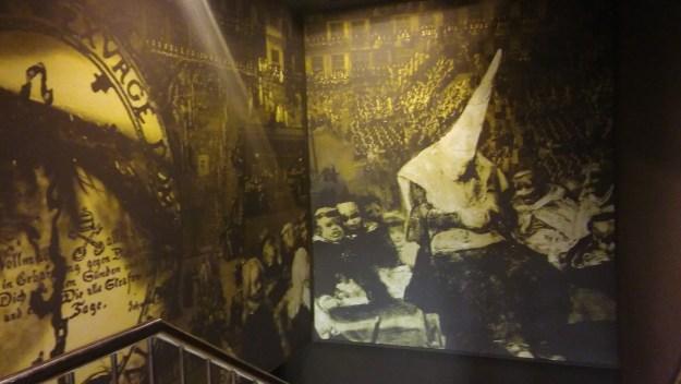 Mural donde se complementa en anterior mostrando a la persona que está siendo sometida a juicio de fe, rodeada de frailes con el hábito dominico. En la esquina inferior izquierda se observa la baranda de la escalera que permite bajar a los restos del Castillo de San Jorge
