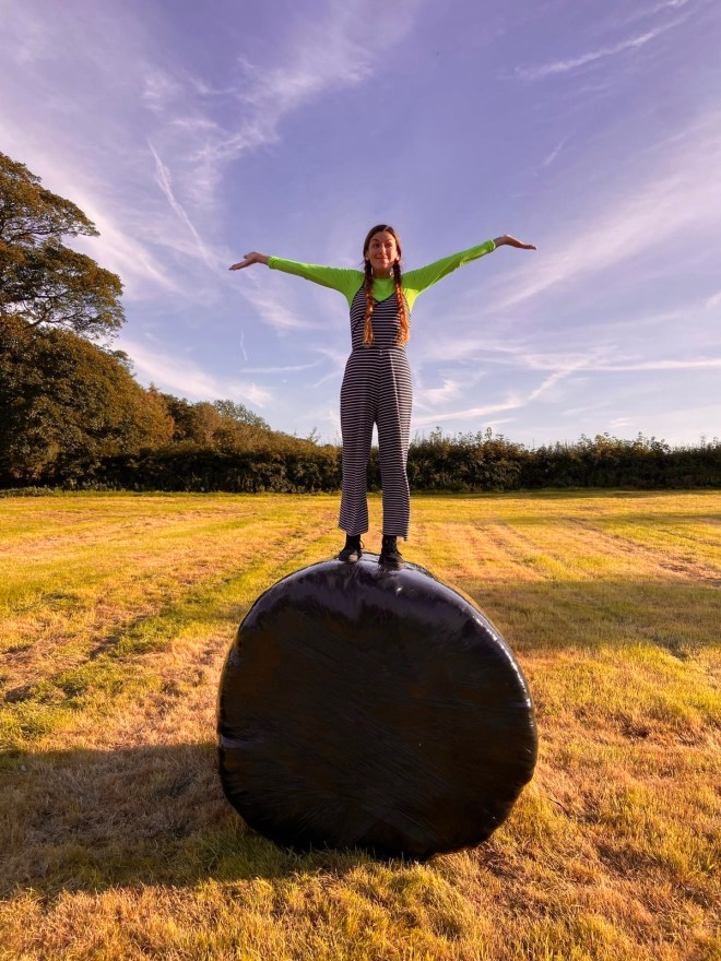 A woman stands on top of a hay bale wrapped in plastic in a field.