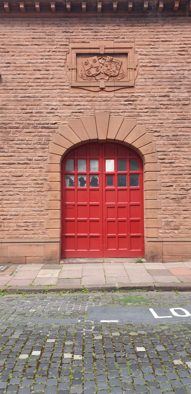 Large red wooden door on a sandstone building with decorative plaque above at Tullie house