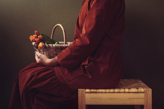 A woman sitting on a woven wooden stool with a handwoven basket on her lap with tulips in.
