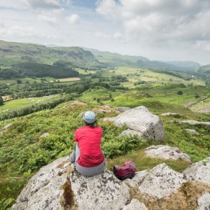 person sits on rock at Eskdale looking over valley