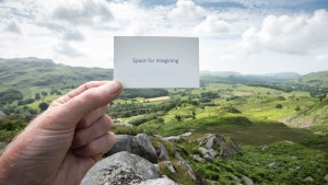 A hand holds up a small card with the words 'space for imagining' on in a rural landscape.