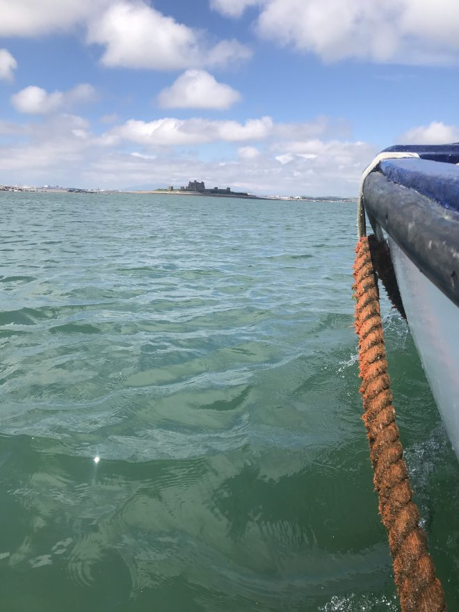 sea and side of boat, piel island in distance.