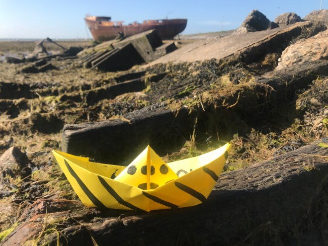 A paper boat sits on a stone in a dock area with seaweed around.