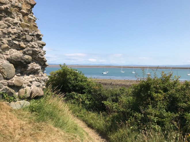 The side of Piel Castle looking out towards the sea with boats.