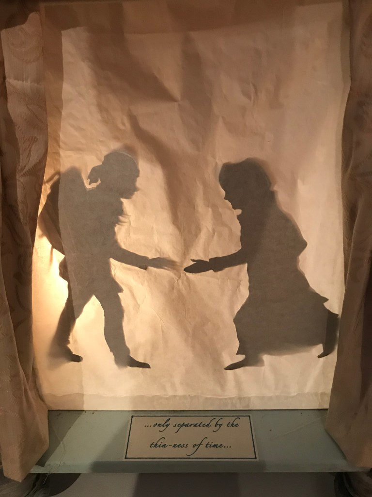 Two figures are seen as shadows, reaching their hands out to one another behind a curtain; the text in front of the figures reads '...only separated by the thin-ness of time ... '