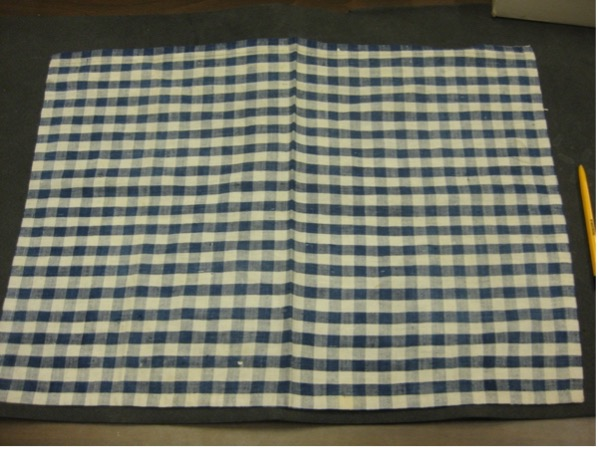 Image shows a cloth known as 'gingham' in two patterns. On the left is a checked blue and white pattern. On the right there are lines in red, yellow and white.