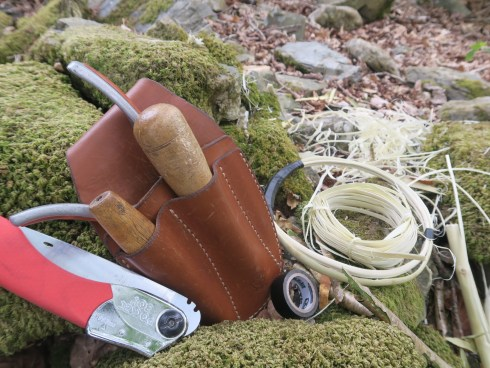 A knife, with red handle, folded in so the blade is not visible; a leather pouch with 2 wooden handled tools in; some curls of stripped hazel; and binding tape; all resting on a moss-covered rock. These are the tools used by Lorna Singleton, weaver and basket maker.