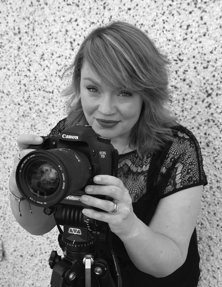 The image shows Rachel Capovila standing beside a pebble-dashed wall, with a Canon camera in front of her, and her finger poised on the button ready to take an image.