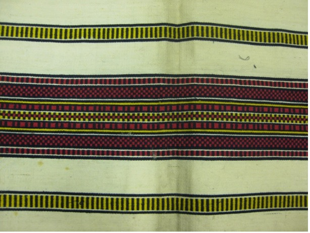 A close up photograph of 19th century gingham cloth, with red and yellow stripes against white, and black markings.
