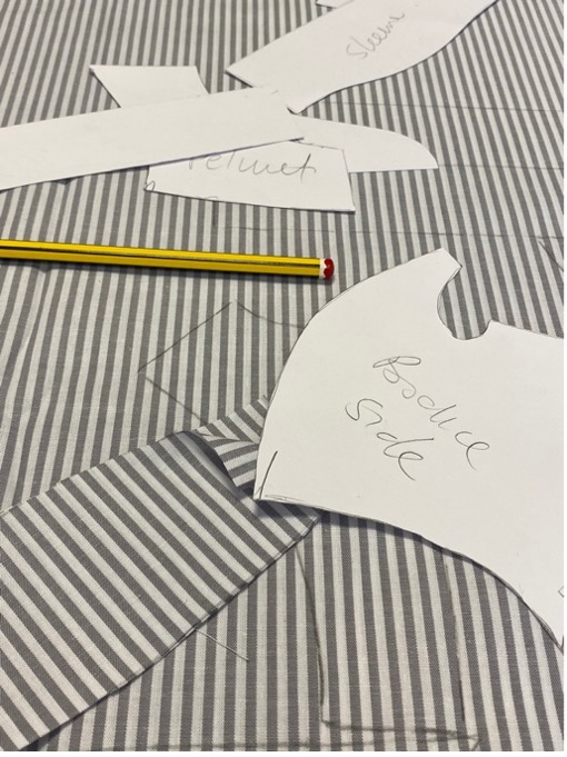 Paper patterns for clothes laid onto striped material.