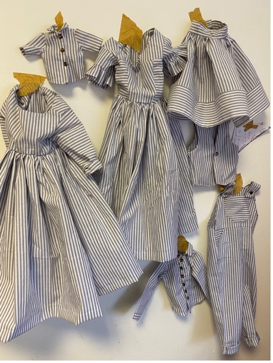Small items of clothing made in striped material, using patterns for clothes that would have been worn by enslaved people living on the plantations in america in the nineteenth century