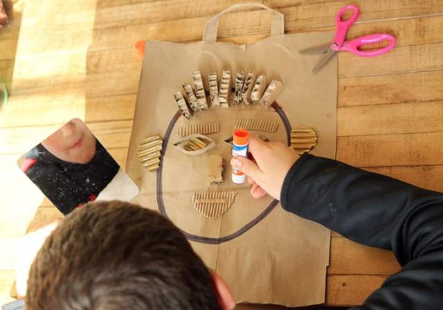 Child looking in mirror while creating self-portrait collage.