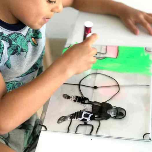 Boy drawing creating mixed media artwork on plexiglass