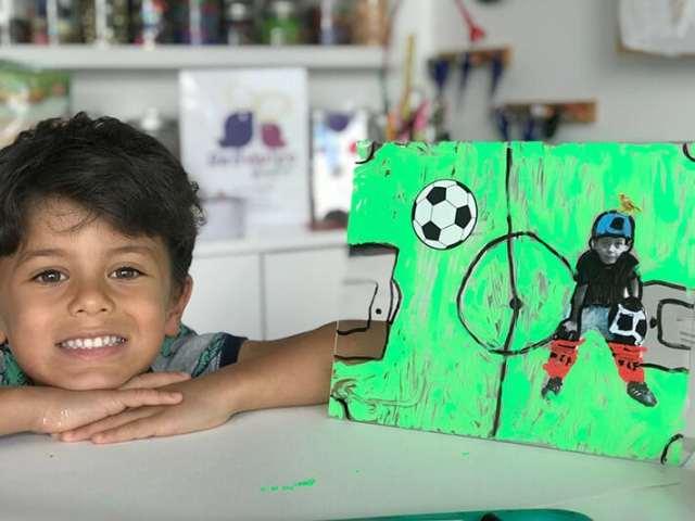 Boy posed next to finished mixed media artwork on plexiglass