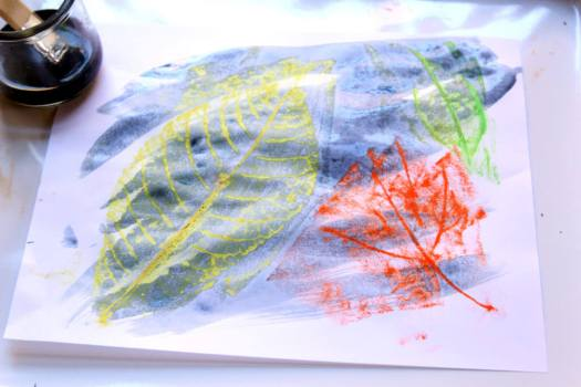 Painting watercolors over crayon leaf rubbings