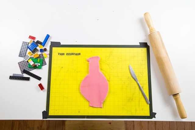 Cut out playdough shapes for LEGO prints using rolling pin, LEGOs, playdough & butter knife