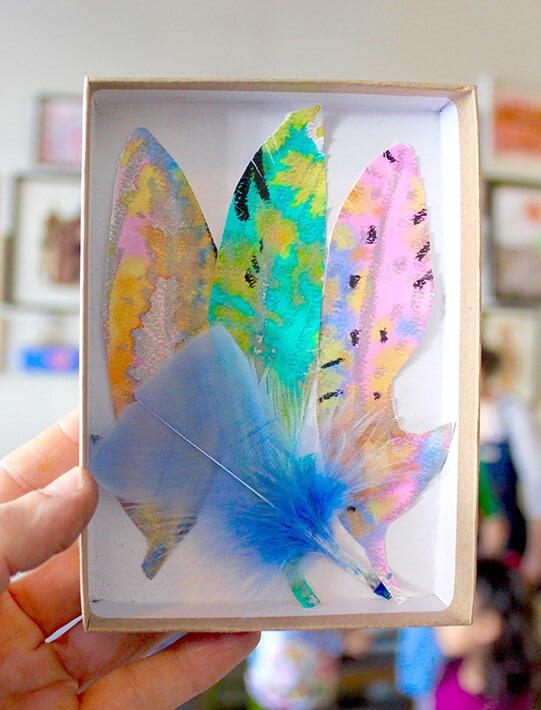 Hand holding box with hand drawn feathers in it & blue bird's feather – nature drawing ideas for kids