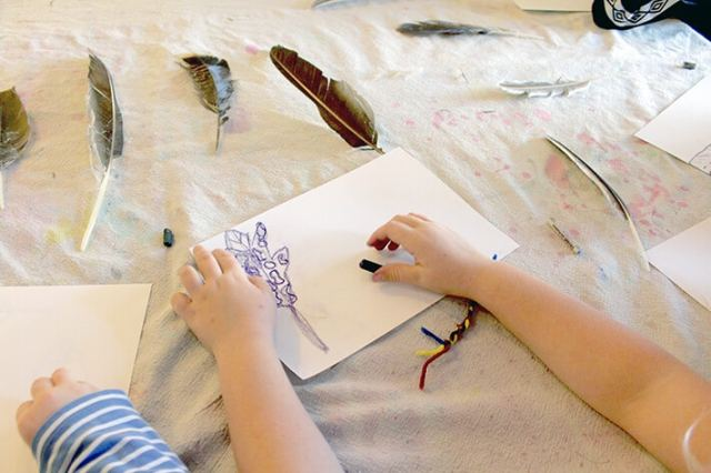 Student holding oil pastel drawing feather on paper with feathers laying on table in this easy nature drawing idea for kids