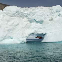 Massive iceberg and view to a tender boat