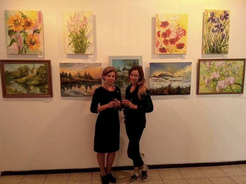 Наталія Жигайло (зліва) на фоні своїх робіт