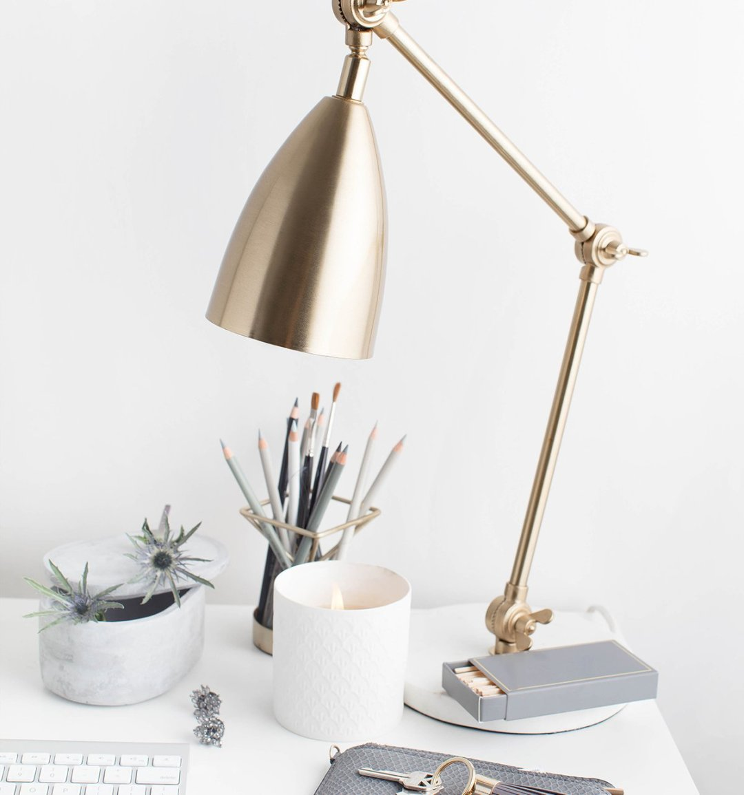 Styled desktop with keyboard, lamp and pencils