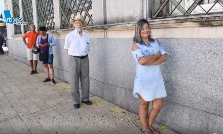 LARGAS FILAS Y ESPACIO DE PERSONAS DELIMITADO.