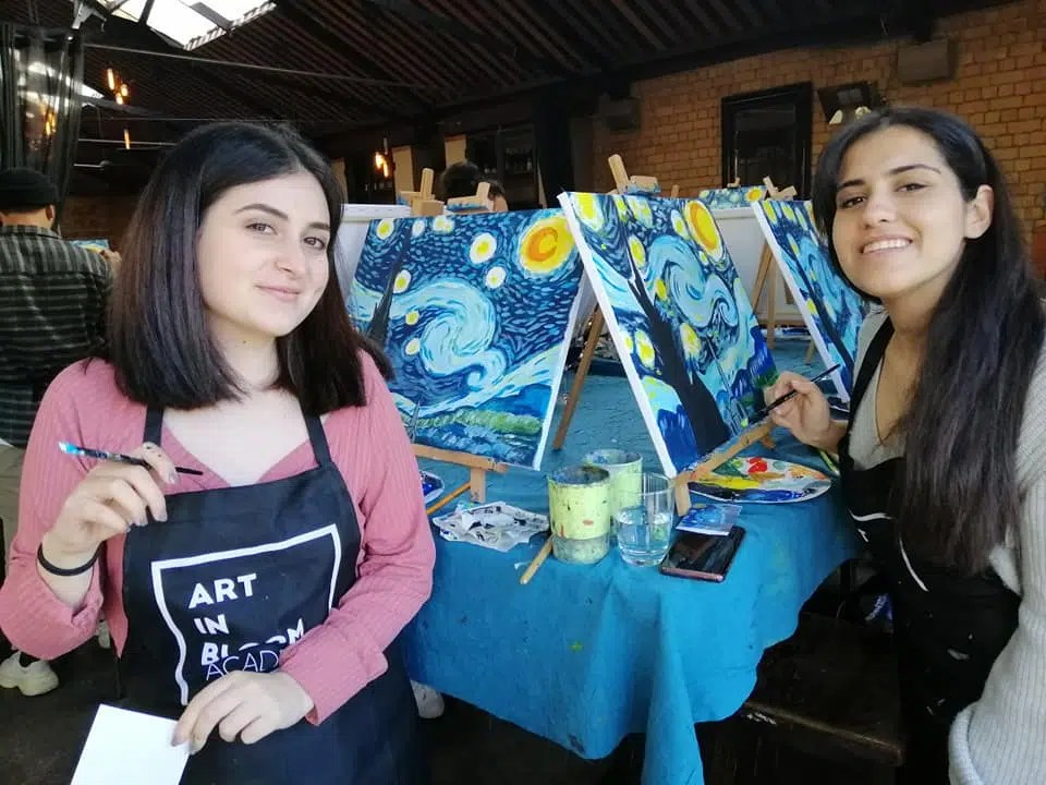 two friends art an Art in Bloom wine and paint party