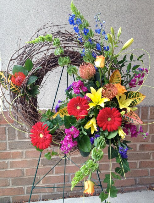 A unique twist on an easel design includes bright colors and unusual blooms.