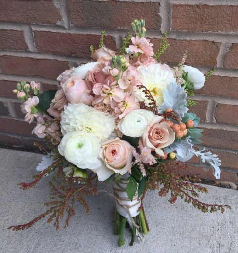 Angela's bouquet of soft blush roses and stock, white ranunculus and dahlias, japonica, dusty miller and succulents.
