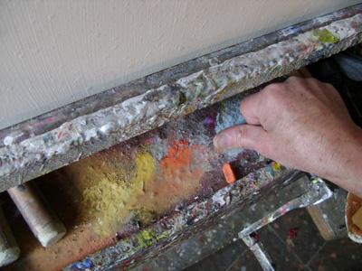 Le peintre imprègne son pouce de pastels tendres orange. The artist imbues his thumb with orange.