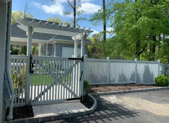 White vinyl fence and gate with a custom arbor