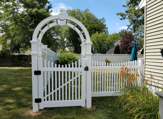 White vinyl picket fence and gate with scalloped top with arbor over the top of the gate leading into the backyard